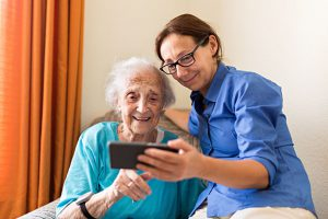 carer and elderly woman with smartphone
