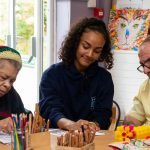 young female volunteer taking part in art work with people with dementia