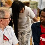 man with dementia speaking with young male volunteer and care manager