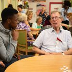 young man talking with older man with dementia