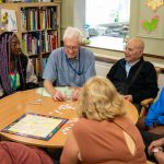 People with dementia and young volunteers playing games around a table
