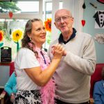 man with dementia dancing with care worker