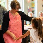older women dancing with young girl at dementia party
