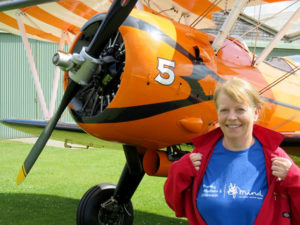 Jane Grieves standing on the ground by an airplane in a BLG Mind t-shirt