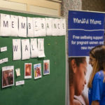 Woman in a BLG Mind t-shirt looking at photos on the Suicide Remembrance Wall at Bromley World Mental Health Day 2019 event