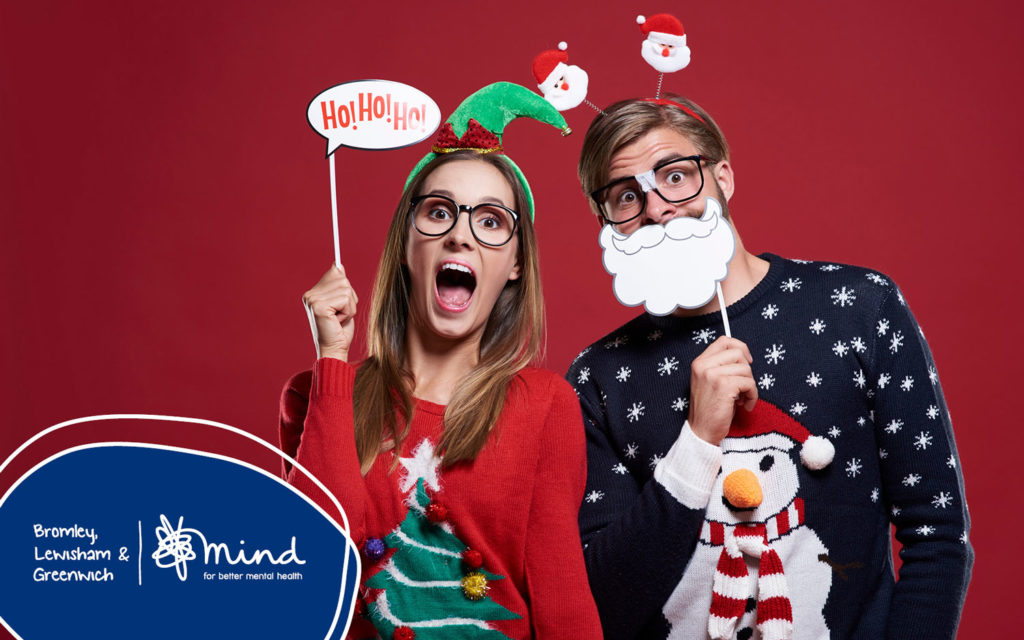 Woman and man wearing glassed, dressed up in Christmas jumpers, decorative head dressings, fake beard and ho-ho-ho sign