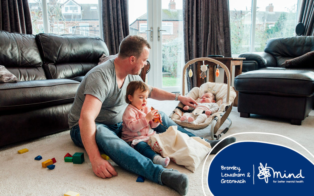 A dad sitting the living room floor, playing with toddler daughter and baby in bouncer