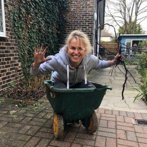 A Trafalgar Marketing volunteer sitting in a wheelbarrow