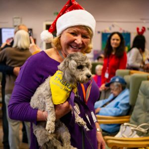 Carol Lock in a Santa hat holding an animal therapy dog