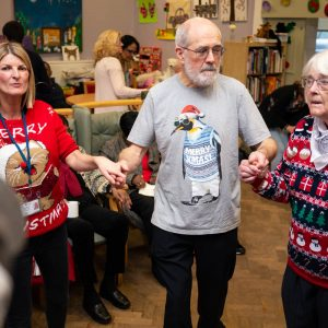 Staff, carers and people with dementia dancing at MindCare Christmas Party