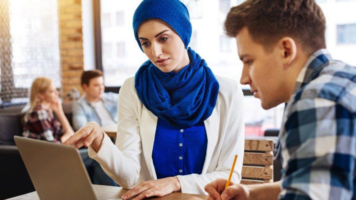 A woman showing a man something in a laptop screen