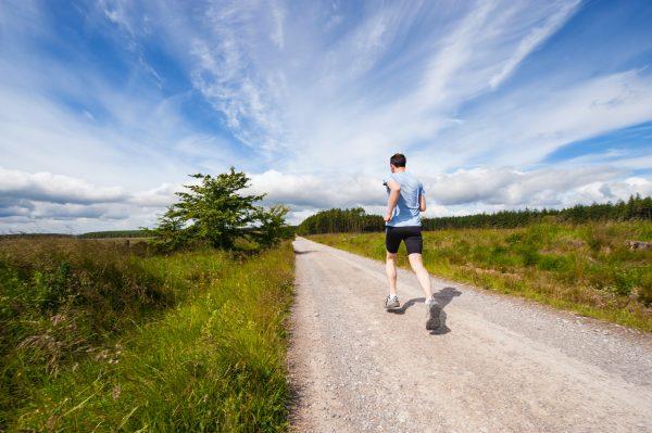 Man running along a path through a field