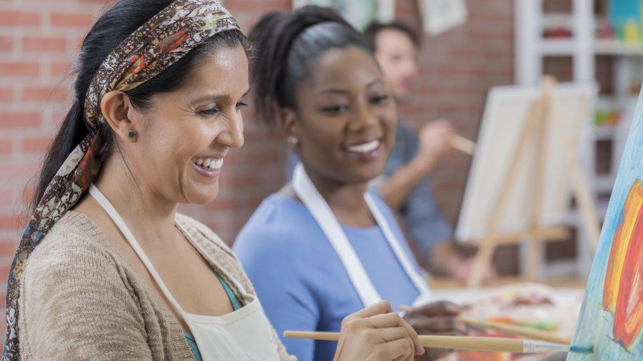 जातीय रूप से विविध महिलाएं एक कला वर्ग का आनंद ले रही हैं।