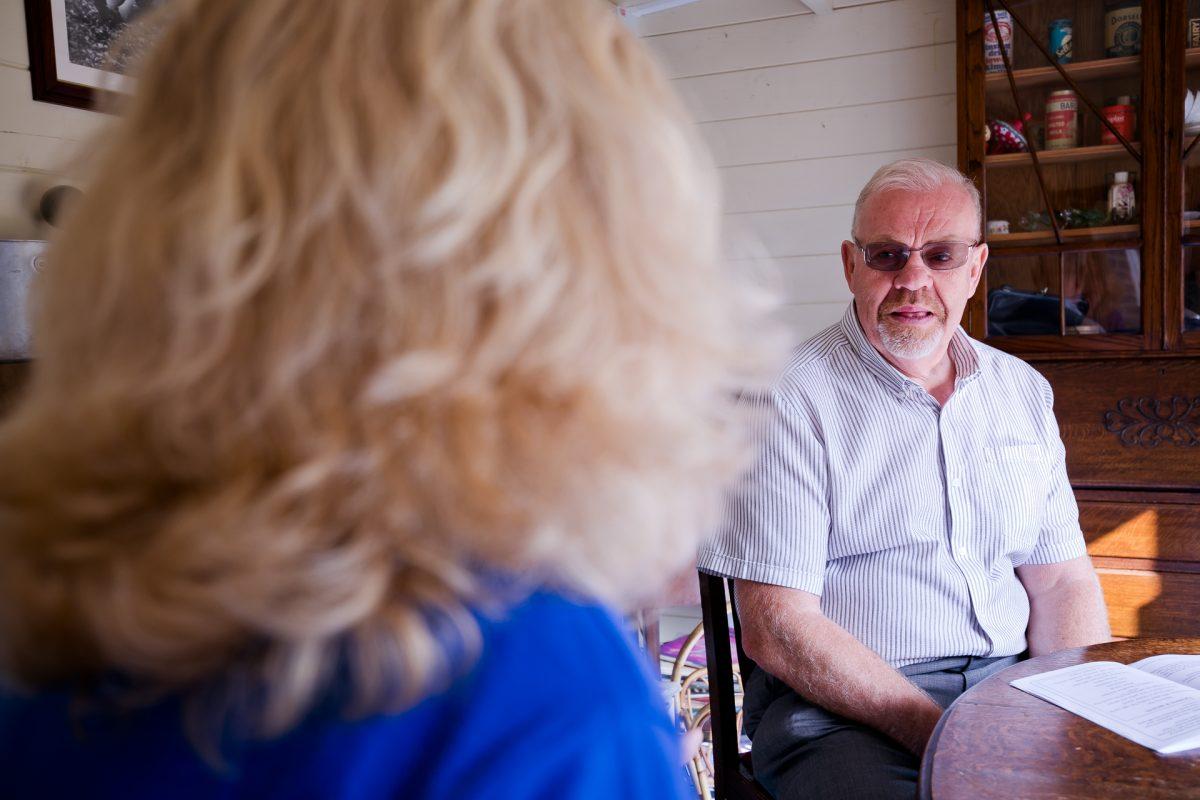 Trabalhadora de apoio à demência falando com uma cliente