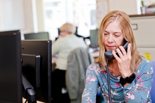 A BLG staff member answering the phone in an office