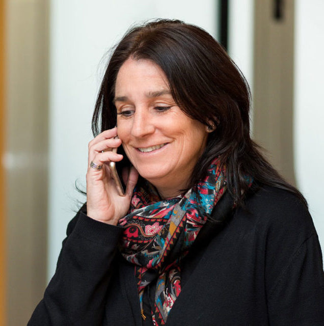 A smiling woman speaking on a telephone