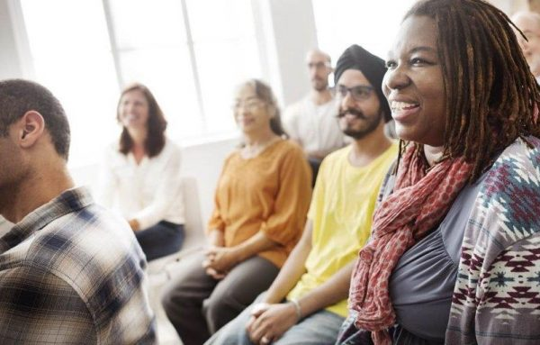 A group of smiling people in a wellbeing session.