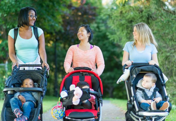 Three women pushing their babies together in buggies
