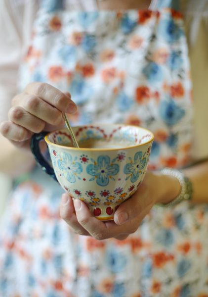 Hands holding a decorative teacup containing tea