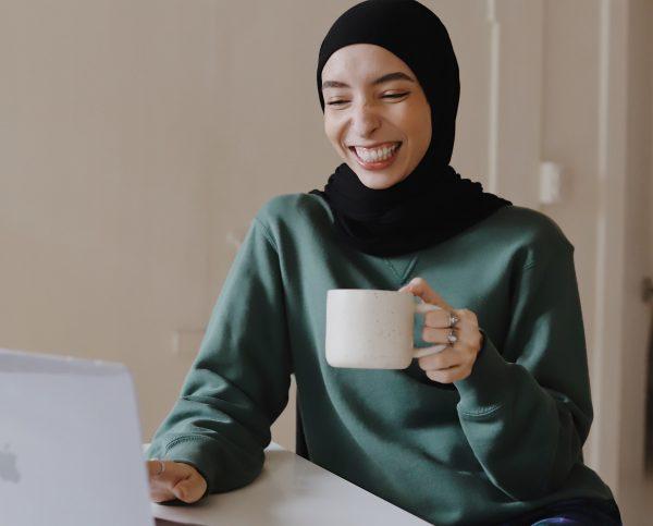 Woman in hijab smiling at laptop screen
