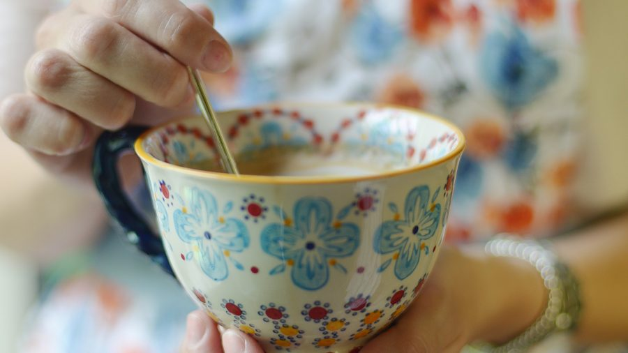 A woman stirring a cup of tea